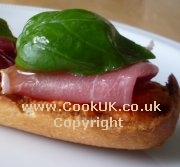 Tomato bread topped with ham and basil