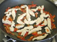 Frying sweet red peppers and chicken